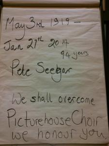 "Flipchart paper which says ""May 3rd 1919-Jan 21st 2014, 94 years, Pete Seegar, We shall overcome, Picturehouse Choir, we honour you"""