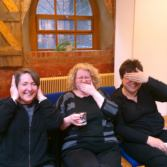 3 choir members being silly - one with hands over ears, another with her hand over her mouth and the third covering her eyes