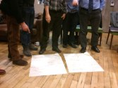 comical photo of the basses pointing at flip chart paper on the floor