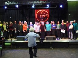 Blurred picture of the choir dancing during a performance with Jules also dancing in the foreground March 2010
