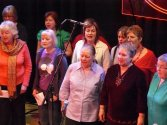Early photo of a Picturehouse performance including several people who are still in the choir