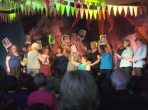 The choir performing an anti-capitalist song holding up images of Murdock on stage at the Streetchoirs festival 2011