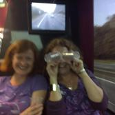 Caroline with a cunning disguise (hiding behind two plastic cups) on the coach on the way home from Sing for Water London 2011